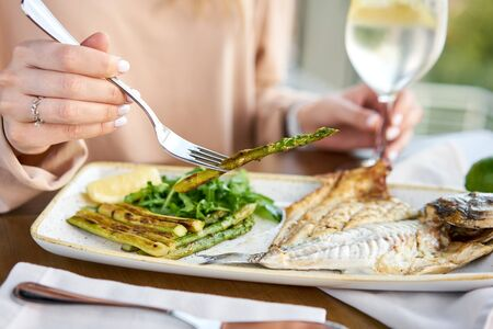 Foto de Lunch in a restaurant, a woman eats roasted dorado fish with grilled asparagus. Dish decorated with a slice of lemon. Restaurant menu - Imagen libre de derechos