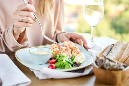 Photo pour Grilled Argentine shrimp with mango-jalapeno sauce. Lunch in a restaurant, a woman eats delicious and healthy food. Delicious fresh seafood prawns with fresh vegetables and lime. Cream sauce - image libre de droit