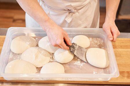Foto de Dough for Neapolitan pizza. Closeup hand of chef baker in uniform white apron cook pizza at kitchen - Imagen libre de derechos