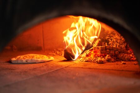 Photo pour Baked tasty margherita pizza in Traditional wood oven in Naples restaurant, Italy. Original neapolitan pizza. Red hot coal - image libre de droit