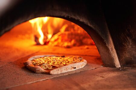 Photo pour Baked tasty margherita pizza in Traditional wood oven in Naples restaurant, Italy. Original neapolitan pizza. Red hot coal. - image libre de droit