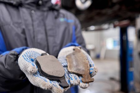 Foto de The mechanic holds the old and new brake pads in his hand. Change the old to new brake disc on car in a garage. Auto repair concept. - Imagen libre de derechos