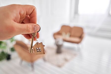 Photo pour Men hand holding key with house shaped keychain. Modern light lobby interior. Mortgage concept. Real estate, moving home or renting property. - image libre de droit