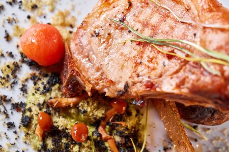 Photo pour Pork meat on the bone with baked potatoes decorated with pickled cherry tomatoes. Photos for cafe and restaurant menus - image libre de droit