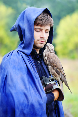 handsome young man in a raincoat with a falcon in his hand