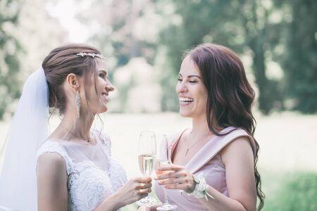 Foto de newlyweds with guests drink champagne in the park - Imagen libre de derechos