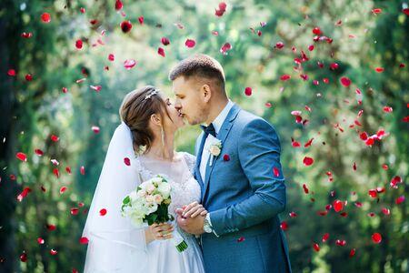 Foto de Portrait of the bride and groom with a bouquet of flowers in the park - Imagen libre de derechos