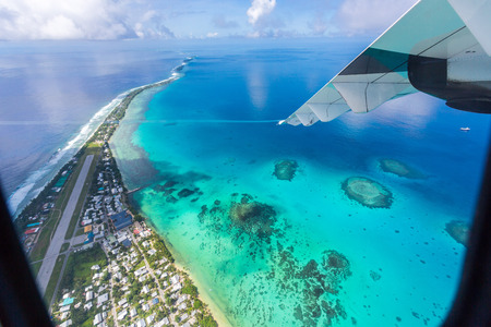 Photo pour Tuvalu under the wing of an airplane. Aerial view of Funafuti atoll and the airstrip of International airport in Vaiaku. Fongafale motu. Island nation in Polynesia, South Pacific Ocean, Oceania. - image libre de droit