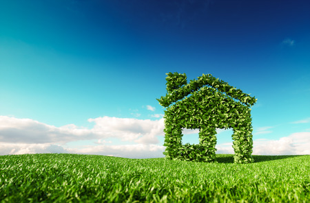 Foto de Eco friendly living concept. 3d rendering of green house icon on fresh spring meadow with blue sky in background. - Imagen libre de derechos
