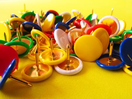 Photo pour Multicolored buttons, cloves on a yellow background. Stationery nails for fastening paper. - image libre de droit
