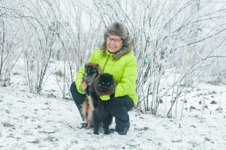 Woman embracing cute dog Pekingese and cat in winter park