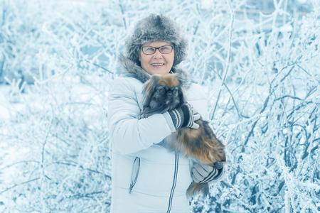 Woman embracing cute dog Pekingese in winter park