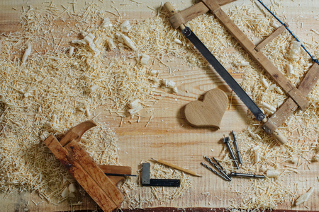 A heart made of wood, a plane, a saw, a square, a pencil and other woodworking tools lie on a wooden rough surface