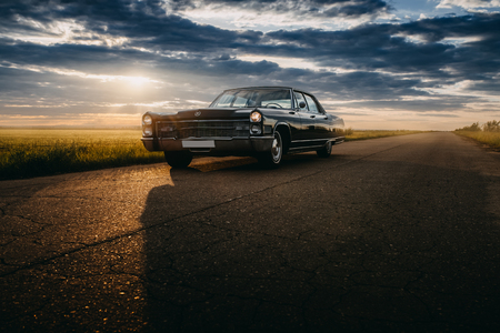 Photo for Engels, Russia - June 08, 2018: Black retro vintage muscle car Cadillac Fleetwood Brougham is parked at countryside asphalt road at golden sunset - Royalty Free Image
