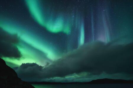Photo for Northern Lights, Aurora Borealis in Kola Peninsula at night sky illuminated green. Murmansk region, Russia - Royalty Free Image
