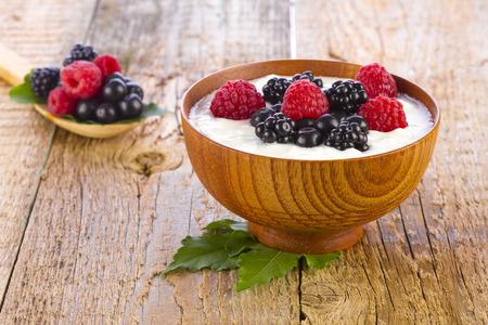 yogurt with wild berries in wooden bowl on wooden background