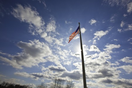 Against a beautiful blue sky and in a strong wind the Stars and stripes waves proudly
