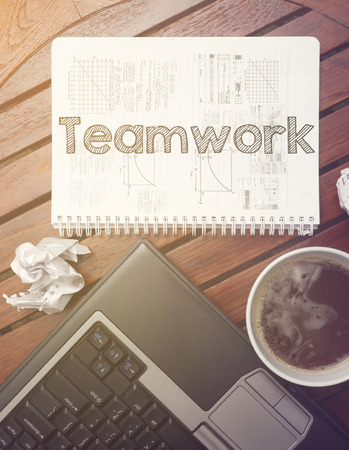 work place - table with notebook with note about: teamwork