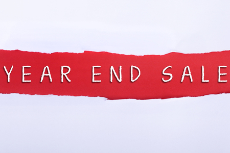 Torn paper with a YEAR END SALE word on red background.
