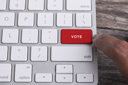 Close up of finger on keyboard button with VOTE word