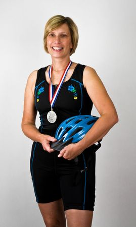 Physically Fit Senior  Boomer Women with Triathlon Gear and Medal