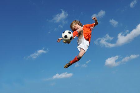 boy playing football kicking ball