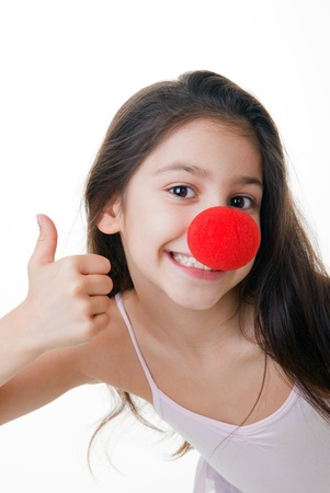 child with red clown nose thumbs up