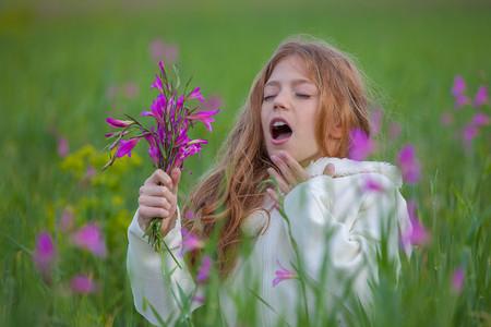 child sneezing allergic to flower pollen in summer