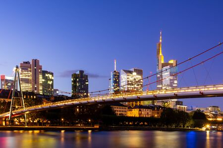 Photo for The Holbeinsteg footbridge in Frankfurt acrross Main river with view to the skyline at night - Royalty Free Image