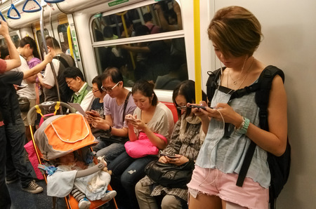Unidentified passengers use their mobile phones in a subway train  Mobile phones and tablets are used for people to entertain and view information when they take public transportation