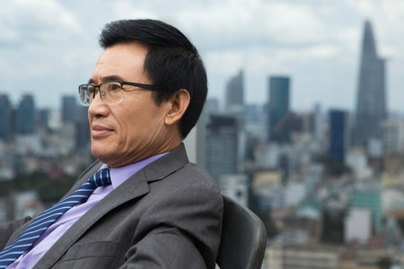 Photo for Close up portrait of thoughtful Asian senior businessman sitting in armchair and looking aside with city view in background. Side view. - Royalty Free Image