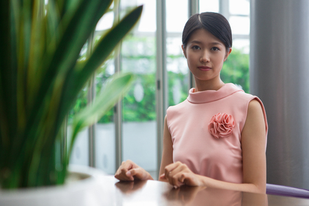 Portrait of content young Asian woman looking at camera and sitting at table in cafe with blurry plant in foreground