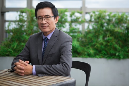 Portrait of content Asian senior businessman looking at camera and sitting at table in cafe with his hands clasped and plants in background