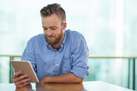Closeup portrait of content middle-aged man using tablet and sitting at cafe table with blurred railing in background. Front view.