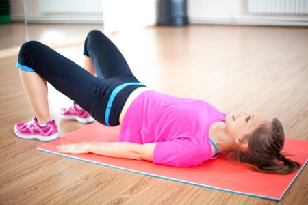 Portrait of happy woman doing abdominal exercise