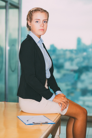 Serious Charming Business Lady Sitting on Table