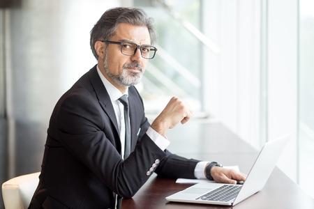 Photo pour Intelligent handsome man with laptop in cafe - image libre de droit