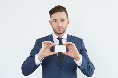 Serious confident young businessman showing card