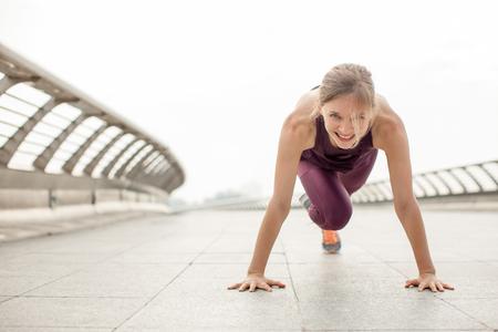 Photo for Girl Doing Mountain Climber Exercise on Bridge - Royalty Free Image