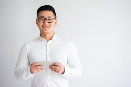 Foto de Happy Young Asian Man Holding Tablet - Imagen libre de derechos