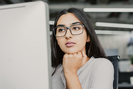 Photo pour Portrait of serious young Latin-American businesswoman wearing eyeglasses working at computer, concentrated female manager looking at monitor with hand on chin - image libre de droit