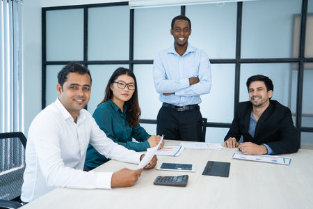Cheerful black managing director and his team in modern office
