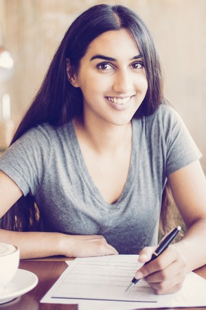 Foto de Diligent Indian student preparing for exam in cafe. Happy young woman working with papers and looking at camera. Positive student enjoying education. Doing homework concept - Imagen libre de derechos