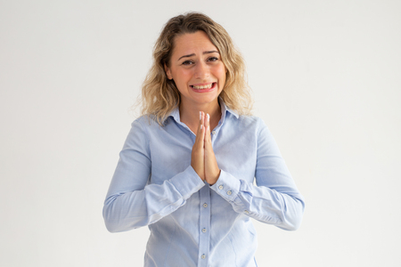 Photo for Scared young woman holding hands together and begging. Upset curly-haired female employee praying and asking about forgiveness. Despair concept - Royalty Free Image