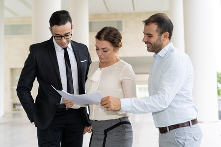 Smiling coworkers checking business documents at meeting. Business partners discussing contract before concluding a deal. Negotiation process concept
