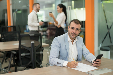 Handsome business man working, using smartphone, looking at camera and writing at desk in office. Two colleagues standing in background. Office work concept.