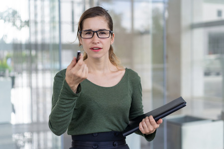 Puzzled office nerd staring at you through glasses. Pensive young woman in eyewear holding folder and pointing pen at camera, office building exterior in background. Selection concept