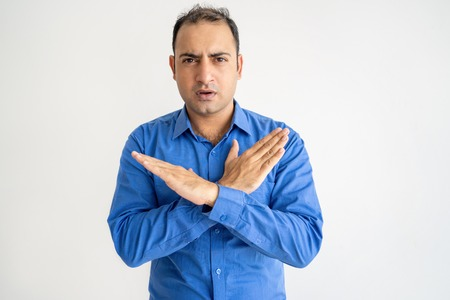 Serious man showing crossed hands and looking at camera. Indian guy denying something. Prohibition concept. Isolated front view on white background.