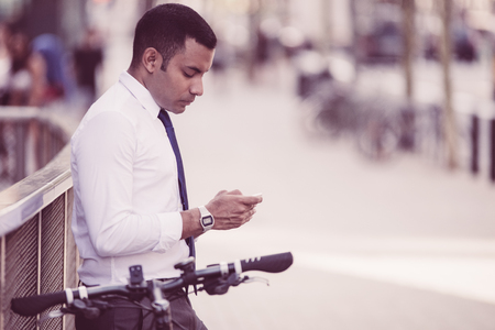 Calm Latin male manager texting message on phone outdoors while standing near railing with bicycle. Thoughtful young Hispanic businessman using smartphone to make note. Gadget for convenience concept