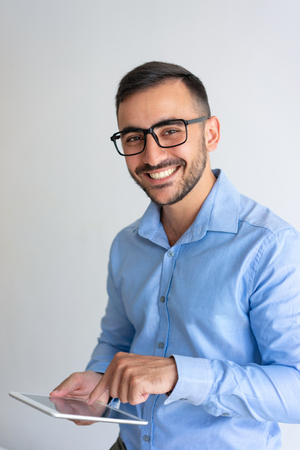 Photo pour Cheerful businessman testing mobile PC app. Young man in glasses and casual shirt using tablet and smiling at camera. Information technology concept - image libre de droit